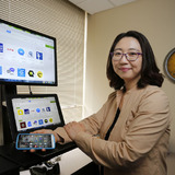 Su 君g Kim in her office with laptop and mobile phone