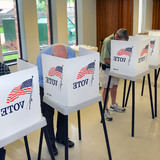 Voters casting ballots in election booth