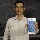 Ying Cai holding phone in his lab