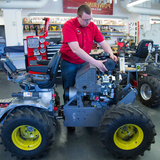 An ISU student works on a new quarter scall tractor inside a workshop